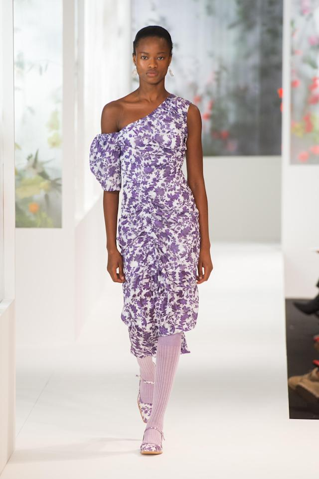 <p><i>Model wears a purple, floral-printed one-shoulder dress, exposing one shoulder. (Photo: ImaxTree) </i></p>