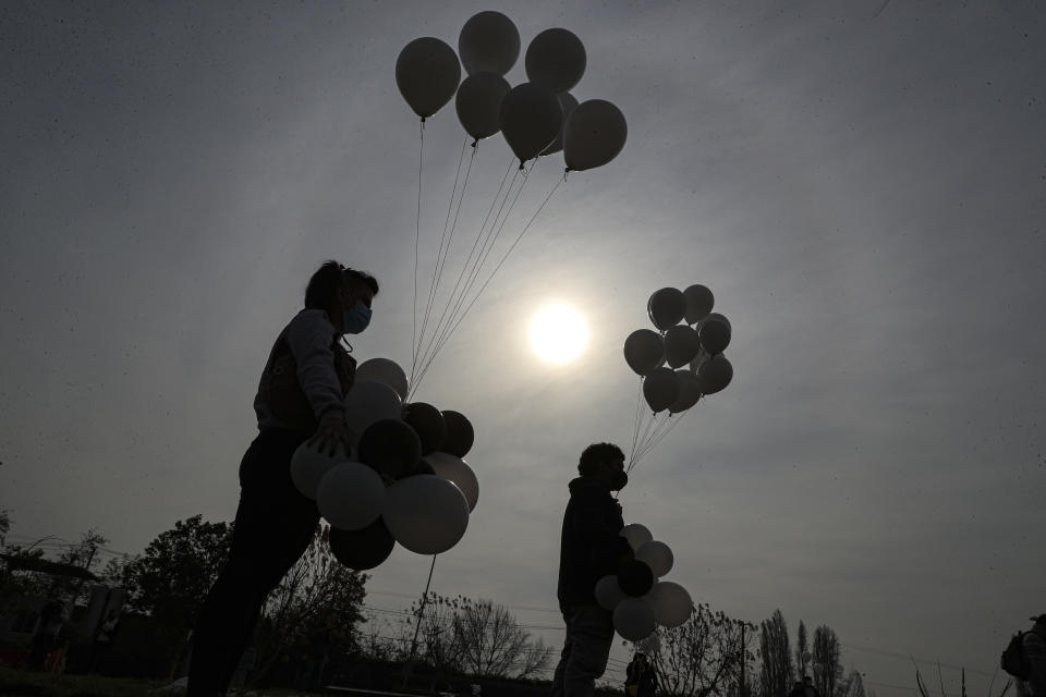 Relatives carry white balloons to the funeral of 72-year-old Monica Lagos at the Manantial cemetery in Santiago, Chile, Monday, June 15, 2020. According to her grandaughter Ninoska Vasquez, who works as an assistant at a health center, Lagos died from complications related to COVID-19. (AP Photo/Esteban Felix)