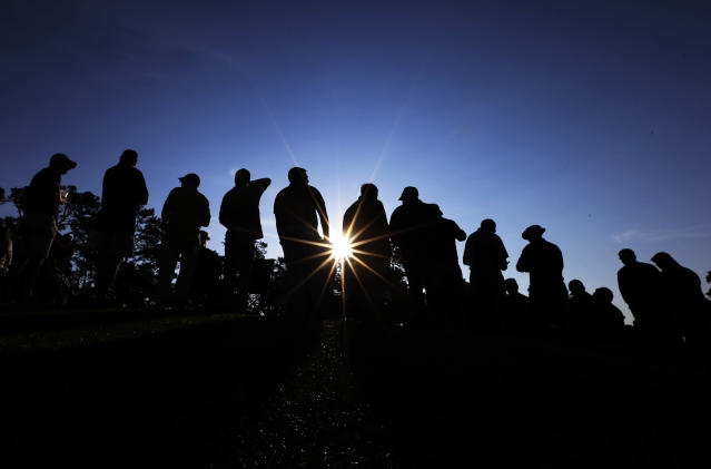 Spectators wait for golfers as the sun rises during the second round of the Masters golf tournament Friday, April 11, 2014, in Augusta, Ga. (AP Photo/David J. Phillip)