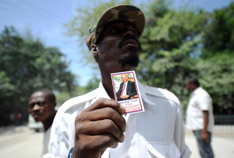 A supporter of former Haitian President Jean Bertrand Aristide holds a picture of Aristide outside his residence on September 10, 2014 in Port-au-Prince