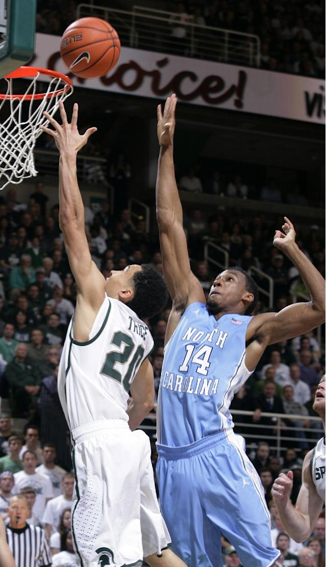 Michigan State's Travis Trice (20) puts up a layup against North Carolina's Desmond Hubert (14) during the first half of an NCAA college basketball game, Wednesday, Dec. 4, 2013, in East Lansing, Mich. (AP Photo/Al Goldis)