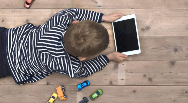 a kid laying on a floor playing with a tablet instead of toy cars that sit next to him