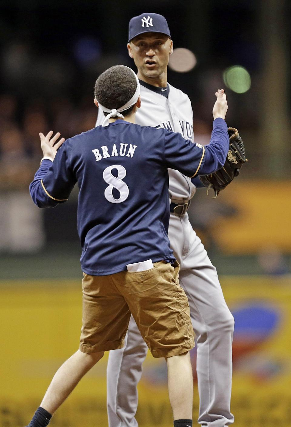 A fan runs out on the field to New York Yankees' Derek Jeter in the sixth inning of a baseball game against the Milwaukee Brewers, Friday, May 9, 2014, in Milwaukee. (AP Photo/Jeffrey Phelps)