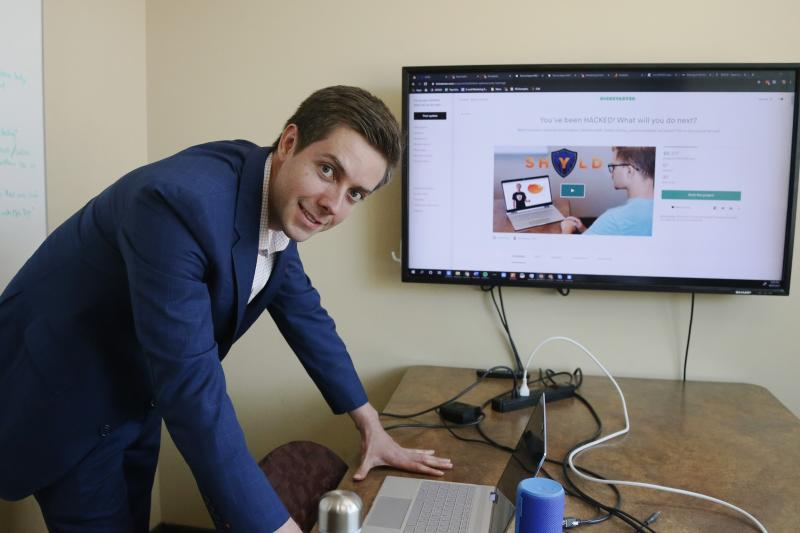 In this Aug. 27, 2019 photo, Tyler Olson poses in hits office at the University of St. Thomas Minneapolis campus. Olson is just starting a cybersecurity company. (AP Photo/Jim Mone)