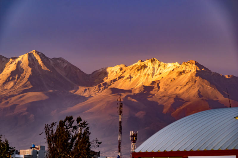 Misti and Pichu Pichu volcano seen from Arequipa Peru in a sunset. Some trees and houses are in the front of the scene
