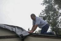 Shawn Frazier, 61, reinforces tarps over his Tampa home's roof ahead of Tropical Storm Elsa on Tuesday, July 6, 2021. Frazier said there was some leaking he caught during a recent rainy day. (Ivy Ceballo/Tampa Bay Times via AP)
