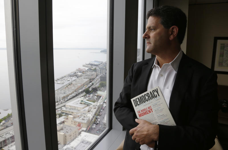 """In this Aug. 2, 2013 photo, Venture capitalist Nick Hanauer poses for a photo by the window of his office in downtown Seattle. Washington state already has the nation's highest state minimum wage at $9.19 an hour, and Hanauer endorses calls to raise it, because he feels putting money in the hands of regular consumers could reduce the drop in demand for goods that he says has hurst our economy. Hanauer is holding a copy of """"Democracy: A Journal of Ideas,"""" that has an article in it he co-authored that promotes an economy driven by a strong middle class. (AP Photo/Ted S. Warren)"""