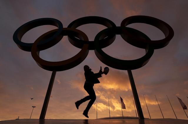 AP10thingsToSee - A woman poses for a photo with the Olympic rings in Olympic Park as preparations continue for the 2014 Winter Olympics in Sochi, Russia on Wednesday, Feb. 5, 2014. (AP Photo/Charlie Riedel, File)