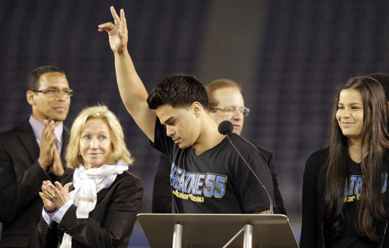 Tyler Seau, center, the son of Junior Seau, reacts to fans during a public memorial service for the late NFL football player Junior Seau at Qualcomm Stadium Friday, May 11, 2012, in San Diego. At rear are pastor Miles McPherson, left, San Diego Chargers owner Dean Spanos, second from right, his wife Susie Spanos, second from left, and Seau's daughter, Sydney Seau. Seau committed suicide on May 2 at his Oceanside, Calif., home. He played parts of 20 seasons in the NFL, with the SanDiego Chargers, Miami Dolphins and New England Patriots. (AP Photo/Gregory Bull)