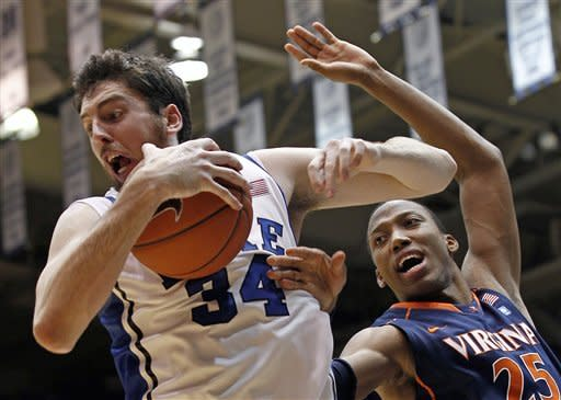 Duke's Ryan Kelly (34) and Virginia's Akil Mitchell (25) struggle for a rebound during the first half of an NCAA college basketball game in Durham, N.C., Thursday, Jan. 12, 2012. (AP Photo/Gerry Broome)