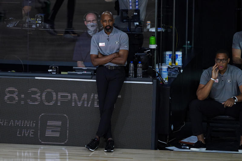 Jacque Vaughn stands on the sideline.