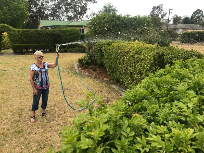 Diane Baxter hoses her garden as she did on Saturday to protect her home when raging bushfires swept past her home town of Yanderra