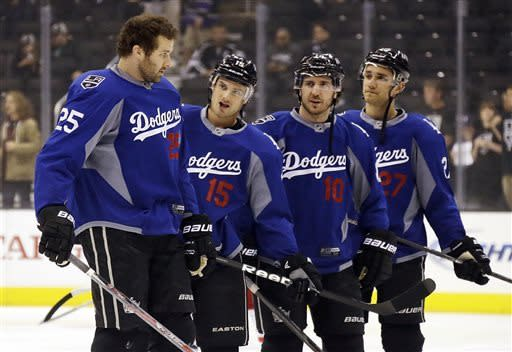 From left, Los Angeles Kings left wing Dustin Penner (25), center Brad Richardson (15), center Mike Richards (10) and defenseman Alec Martinez (27) warm up wearing Los Angeles Dodgers jerseys before an NHL hockey game against the Columbus Blue Jackets in Los Angeles, Thursday, April 18, 2013. (AP Photo/Reed Saxon)