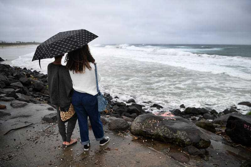 Two women watch stormy conditions at Byron Bay, NSW.