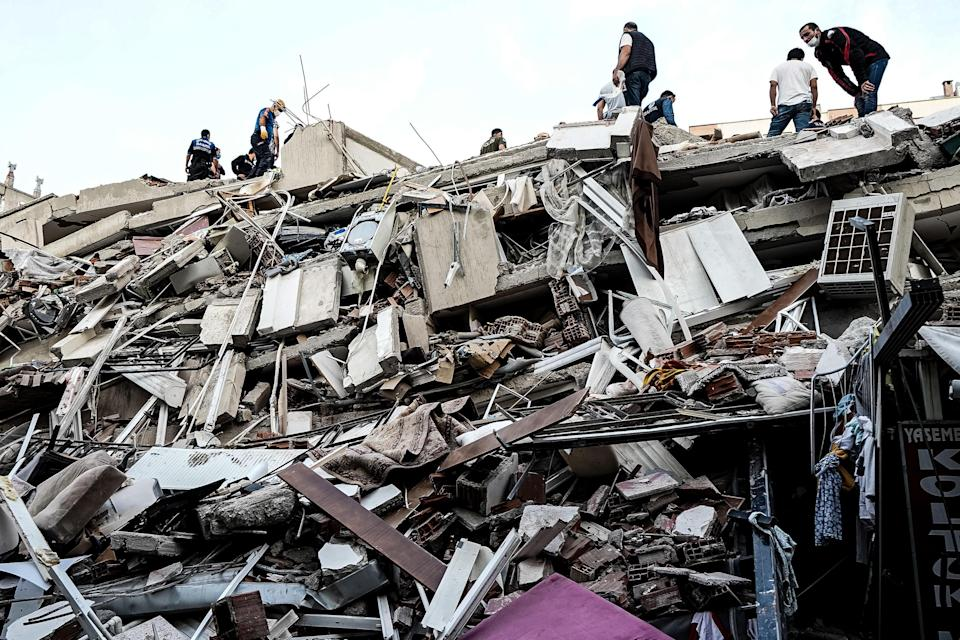 Emergency services personnel search a collapsed building for survivors after a powerful earthquake struck on October 30, 2020, in Izmir, Turkey. / Credit: Usame Ari / Getty