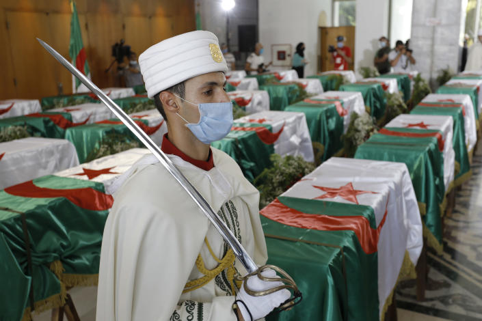 FILE - In this July 3, 2020 file photo, a soldier guards the remains of 24 Algerians at the Moufdi-Zakaria culture palace in Algiers, Friday, July, 3, 2020. After decades in a French museum, the skulls of 24 Algerians decapitated for resisting French colonial forces were formally repatriated to Algeria. French President Emmanuel Macron wants to take further steps to reckon with France's colonial-era wrongs in Algeria but is not considering an official apology, his office said.(AP Photo/Toufik Doudou, File)