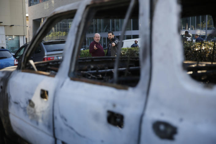 People look at a burned car that was set on fire early Tuesday by supporters of the Shiite Hezbollah and Amal Movement groups, in Beirut, Lebanon, Tuesday, Dec. 17, 2019. Supporters of Lebanon's two main Shiite groups Hezbollah and Amal clashed with security forces and set fires to cars in the capital early Tuesday, apparently angered by a video circulating online that showed a man insulting Shiite figures.(AP Photo/Hussein Malla)