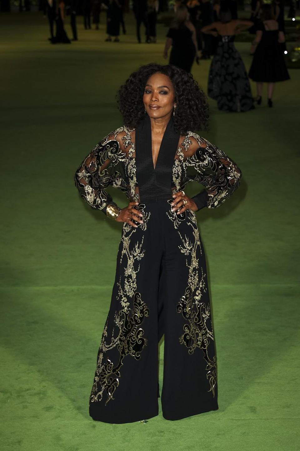 A woman in a patterned, black jumpsuit posing on a green carpet