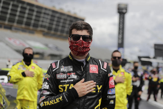 Erik Jones stands during the national anthem before a NASCAR Cup Series auto race at Atlanta Motor Speedway, Sunday, June 7, 2020, in Hampton, Ga. (AP Photo/Brynn Anderson)