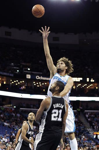 New Orleans Hornets center Robin Lopez shoots over San Antonio Spurs power forward Tim Duncan (21) in the first half of an NBA basketball game in New Orleans, Wednesday, Oct. 31, 2012. (AP Photo/Gerald Herbert)