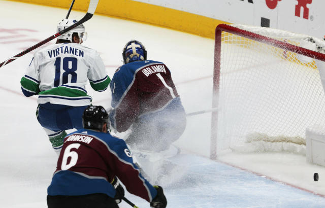 Vancouver Canucks right wing Jake Virtanen (18) scores against Colorado Avalanche goaltender Semyon Varlamov (1) in the first period of an NHL hockey game in Denver, Saturday, Feb. 2, 2019. (AP Photo/Joe Mahoney)