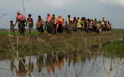 Displaced Rohingya refugees from Rakhine state in Myanmar carry their belongings as they flee violence, near Ukhia, near the border between Bangladesh and Myanmar on September 4 - Credit: K.M. ASAD/AFP