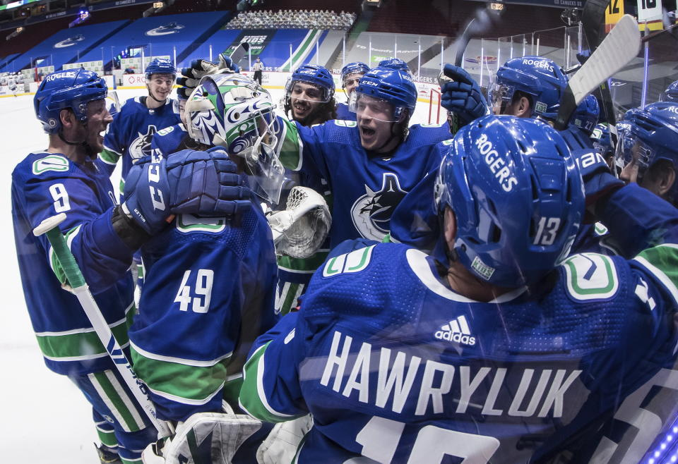 Vancouver Canucks' J.T. Miller (9), goalie Braden Holtby (49) and Brock Boeser (6) celebrate with teammates after the winning goal during overtime of an NHL hockey game against the Toronto Maple Leafs in Vancouver, British Columbia, Sunday, April 18, 2021. (Darryl Dyck/The Canadian Press via AP)
