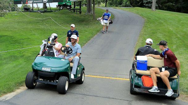 PHOTO: Max Homa and his caddie ride in a cart during a delay due to inclement weather during the second round of the Workday Charity Open on July 10, 2020, at Muirfield Village Golf Club in Dublin, Ohio. (Sam Greenwood/Getty Images)