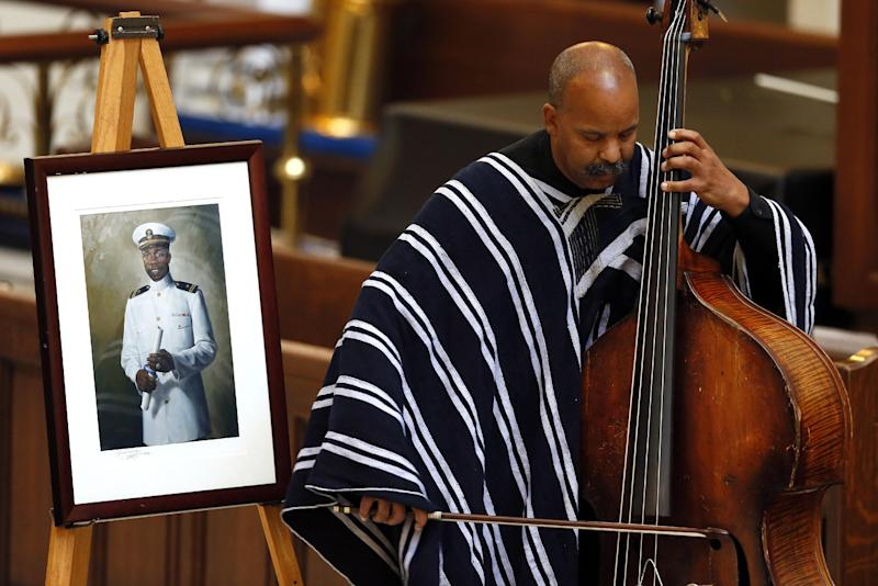 "Wesley Brown, Jr., performs ""Amazing Grace"" during a memorial service for his father, Lt. Cmdr. Wesley Brown, pictured at left, the first African-American to graduate from the United States Naval Academy, in Annapolis, Md., Wednesday, June 6, 2012. Brown was a veteran of World War II, the Korean War and the Vietnam War before retiring from the Navy in 1969. Brown died last month of cancer. He was 85. (AP Photo/Patrick Semansky)"