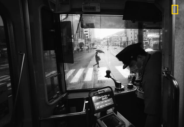 "<p>Photograph and caption by Hiro Kurashina/National Geographic Travel Photographer of the Year Contest. — ""This is a view of the main street from a tram in Nagasaki on a rainy day. The tram is vintage, but retrofitted with modern ticketing equipment. A conductor is no longer on board <span>— </span>only the lone driver. The quiet streetscape seen through the front windshield of the tram somehow caught my attention. This view presents quite a contrast to busy urban centers in Japan, such as Tokyo and Osaka. The ride on a vintage tram through the relatively quiet main street was a memorable experience during our weeklong visit to the historic city of Nagasaki."" Nagasaki, Japan. </p>"