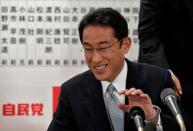 Japan's ruling Liberal Democratic Party policy chief Fumio Kishida smiles as he speaks with the media after Japan's lower house election at the LDP headquarters in Tokyo