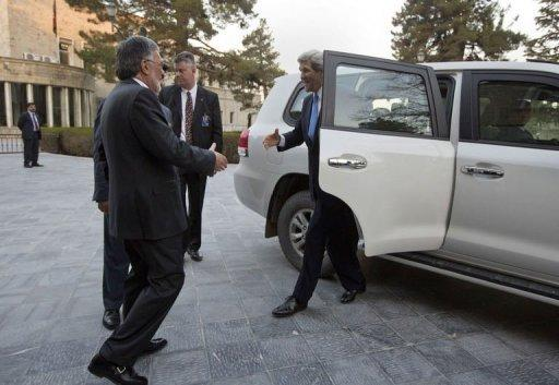 US Secretary of State John Kerry (R) is greeted by Afghan Foreign Minister Zalmai Rassoul (L) on his arrival prior to a meeting with Afghan President Hamid Karzai at the Presidential Palace in Kabul on March 25, 2013