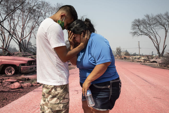 FILE - In this Sept. 10, 2020, file photo, Dora Negrete is consoled by her son Hector Rocha after seeing their destroyed mobile home at the Talent Mobile Estates, in Talent, Ore., after wildfires devastated the region. Two unusual weather phenomena combined to create some of the most destructive wildfires the West Coast states have seen in modern times. (AP Photo/Paula Bronstein, File)