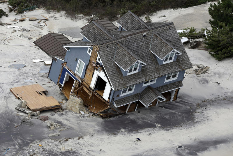 """FILE - This Wednesday, Oct. 31, 2012 file aerial photo shows a collapsed house along the central Jersey Shore coast. Though it's tricky to link a single weather event to climate change, Hurricane Sandy was """"probably not a coincidence"""" but an example of extreme weather events that are likely to strike the US more often as the world gets warmer, the U.N. climate panel's No. 2 scientist told the Associated Press Tuesday, Nov. 27, 2012. (AP Photo/Mike Groll, File)"""