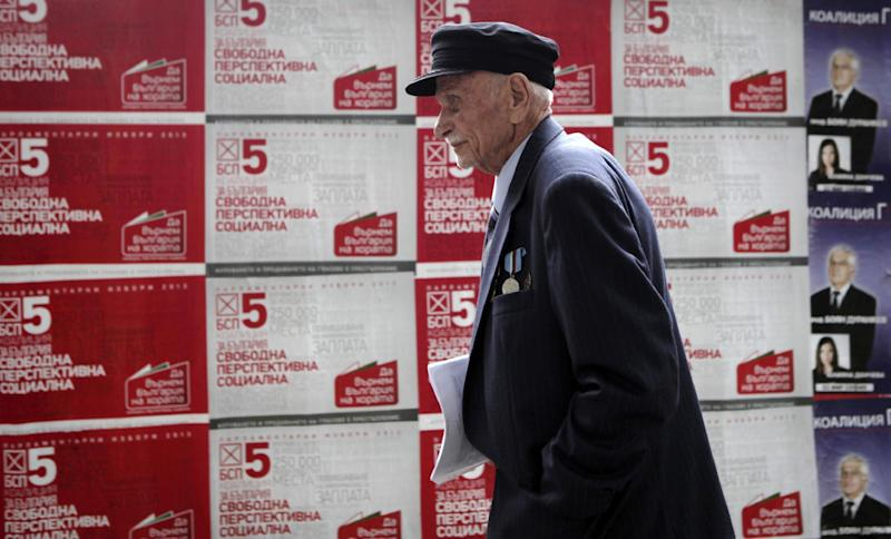 An elderly Bulgarian and World War II veteran passes by election campaign posters in Sofia, Thursday, May 9, 2013. A deeply fragmented Bulgaria heads into parliamentary elections Sunday, as frustration grows over the widening gap between once giddy hopes linked to EU membership and today's sobering reality. (AP Photo/Valentina Petrova)