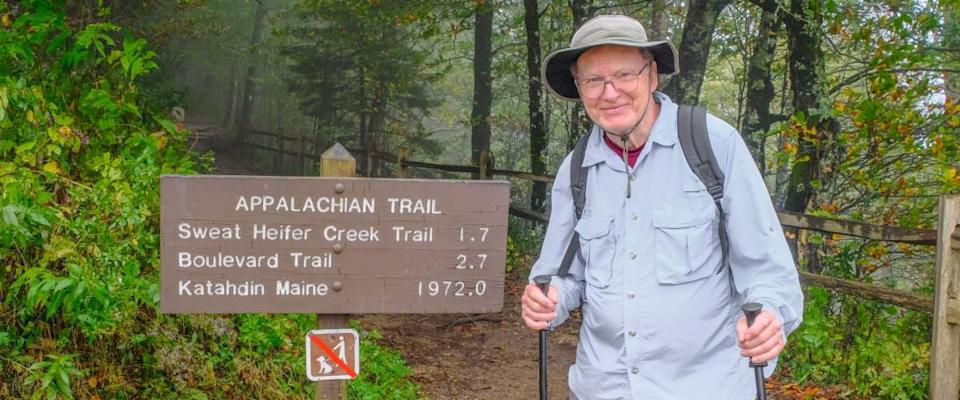 Smiling senior man standing next to Appalachian Trail sign