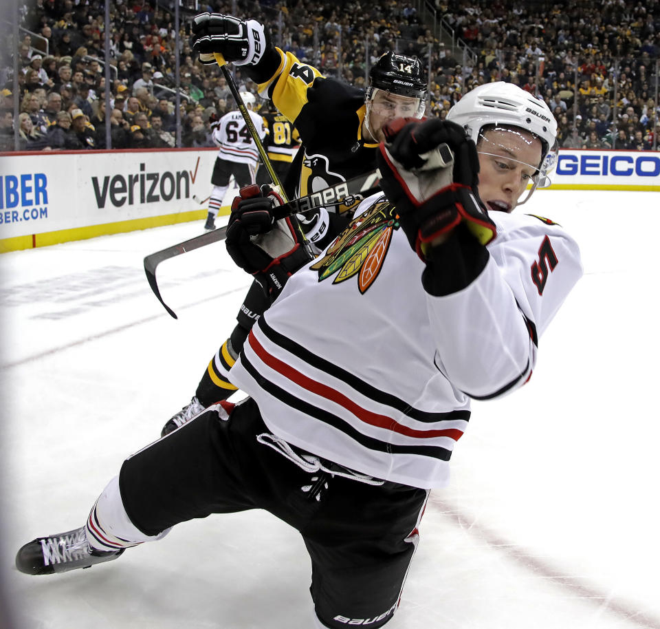 Chicago Blackhawks' Connor Murphy (5) is tripped by Pittsburgh Penguins' Tanner Pearson (14) during the second period of an NHL hockey game in Pittsburgh, Sunday, Jan. 6, 2019. (AP Photo/Gene J. Puskar)