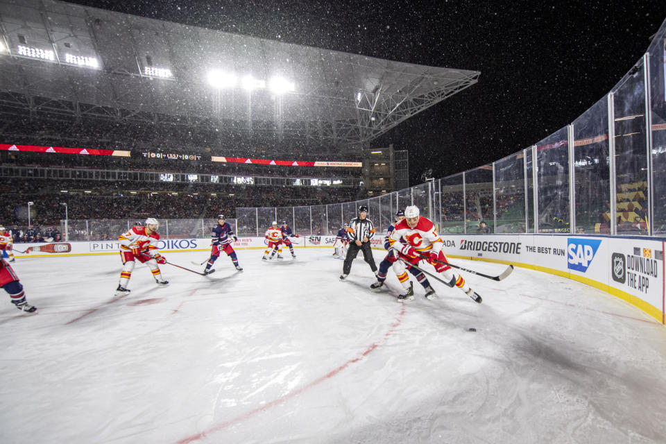 Calgary Flames' Milan Lucic (17) moves the puck against the Winnipeg Jets during the first period of an NHL Heritage Classic outdoor hockey game in Regina, Canada, Saturday, Oct. 26, 2019. (Liam Richards/The Canadian Press via AP)