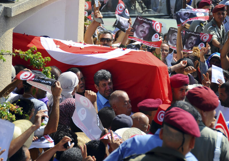 Tunisians carry the coffin of Tunisian opposition politician Mohammed Brahmi out of his home in El Ghazela, in the suburb of Tunis, prior to the funerals in Tunis, Saturday July, 27, 2013. Mohamed Brahmi was shot 14 times in front of his home within sight of his family on Thursday, plunging the country into a political crisis and unleashing demonstrations around the country blaming the government for the assassination. (AP Photo/Hassene Dridi)