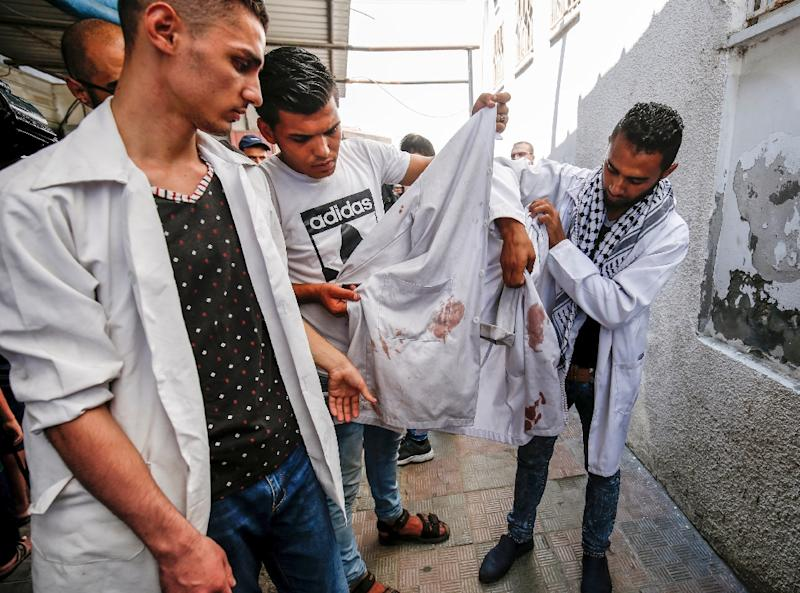 Colleagues of killed 21-year-old Palestinian volunteer medic Abdullah al-Qatati hold up his blood-stained white cloak during his funeral in the Gaza Strip on August 11, 2018, a day after he was killed during protests along the Israel-Gaza border (AFP Photo/SAID KHATIB)