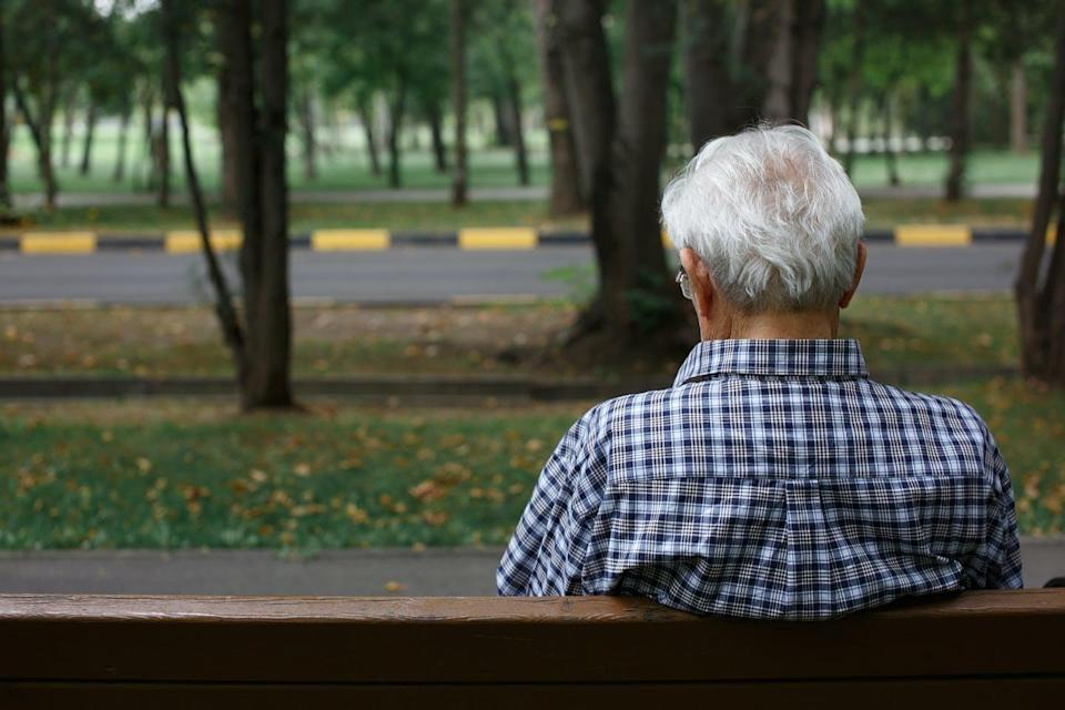 Old man sitting on a park bench.