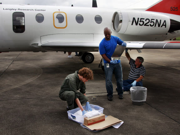 Researcher on NASA's 'bug team' prepare test surfaces to attach to the wings of NASA Langley's HU-25C Falcon aircraft before a flight through the sticky late summer weather in Virginia.