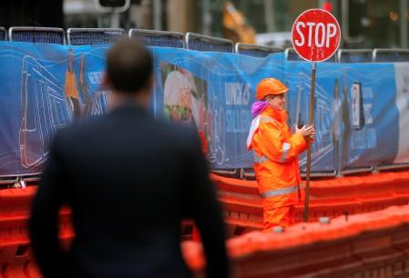A pedestrian walks near a worker directing traffic on a construction site in central Sydney, Australia