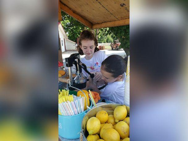 PHOTO: Sisters Hailey and Hannah Hager squeeze lemons at one of their lemonade stands in North Carolina. (Erin Hager)