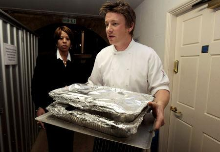 FILE PHOTO: Celebrity chef Jamie Oliver (C) carries out food for a G20 leaders dinner at Downing Street in London April 1, 2009. REUTERS/Christopher Furlong/Pool/File Photo