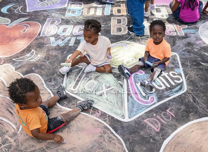 WASHINGTON, DC - JULY 14: Children from the KU Kids Deanwood Childcare Center complete a mural celebrating the launch of the Child Tax Credit on July 14, 2021 at the KU Kids Deanwood Childcare Center in Washington, DC. (Photo by Jemal Countess/Getty Images for Community Change)