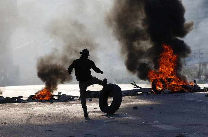 Palestinian protesters set tires on fire during clashes with Israeli troops at the Hawara checkpoint, south of the West Bank city of Nablus, Friday, Dec. 14, 2018. (AP Photo/Majdi Mohammed)