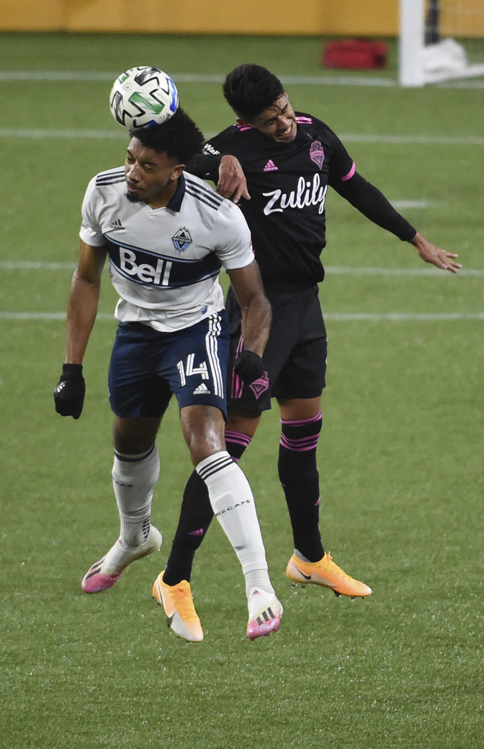 Vancouver Whitecaps forward Theo Bair, left, and Seattle Sounders defender Xavier Arreaga fo up for a head ball during the first half of an MLS soccer match in Portland, Ore., Tuesday, Oct. 27, 2020. (AP Photo/Steve Dykes)