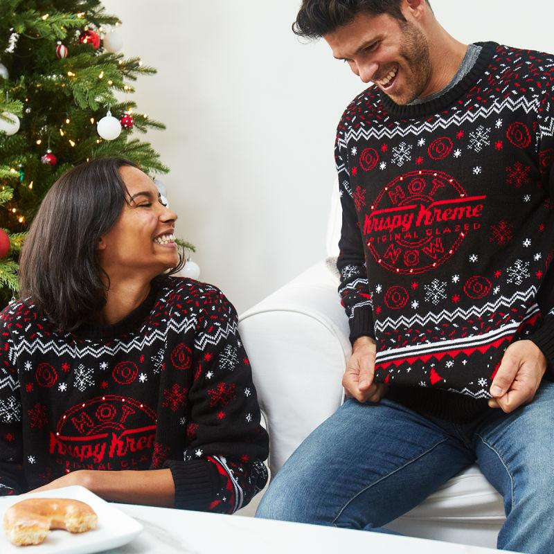 Lifestyle shot of two people in Krispy Kreme holiday sweaters