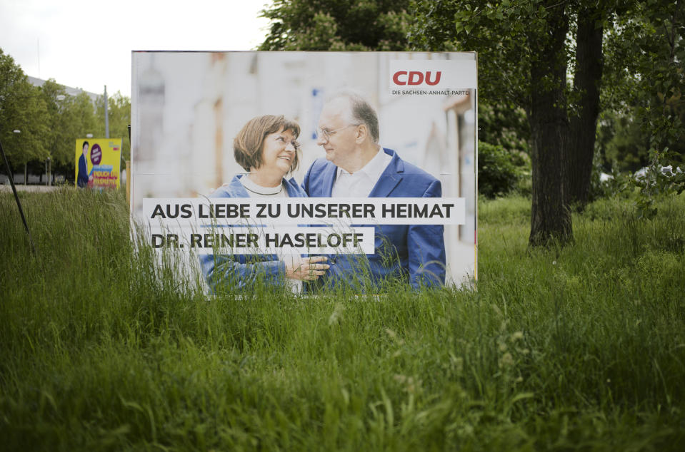 An election campaign poster from the Merkel's Christian Democratic Union, CDU, party stands near a road in the federal state Saxony-Anhalt's capital Magdeburg, Germany, Wednesday, June 2, 2021. The state vote on Sunday, June 6, 2021 is German politicians' last major test at the ballot box before the national election in September that will determine who succeeds Chancellor Angela Merkel. The poster shows ruling CDU governor Reiner Haseloff with bis wife Gabriele Haseloff and the slogan: 'Out of love for our homeland'. (AP Photo/Markus Schreiber)
